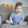 © Margit Grünthal -  Lapse kolmas sünnipäev. Asukoht on lapsele tuttav ja ta tunneb end seal väga hästi. Loomulik valgus ja kelmikus. Mänglevust lisavad taustal olevad apelsinid, mis tähistavad lapse vanust.  Pildistatud Nikon D600+50mm f/1.8